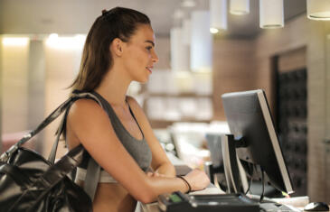 Member retention woman in gym gear at front desk Pexel stock column