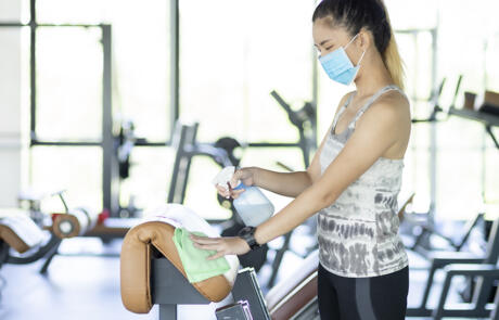 Sales and marketing woman wearing mask cleaning gym equipment Freepik stock column