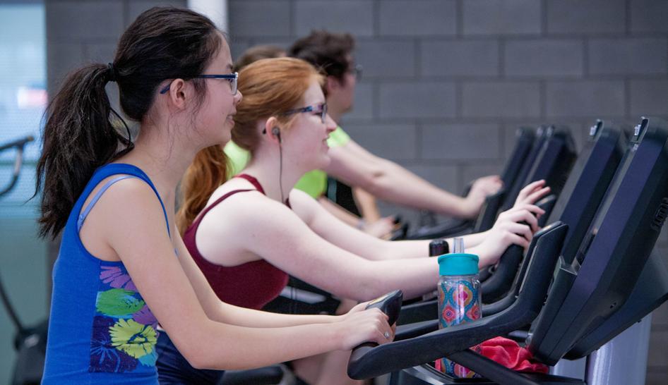 Women In Gym On Bikes Column Width
